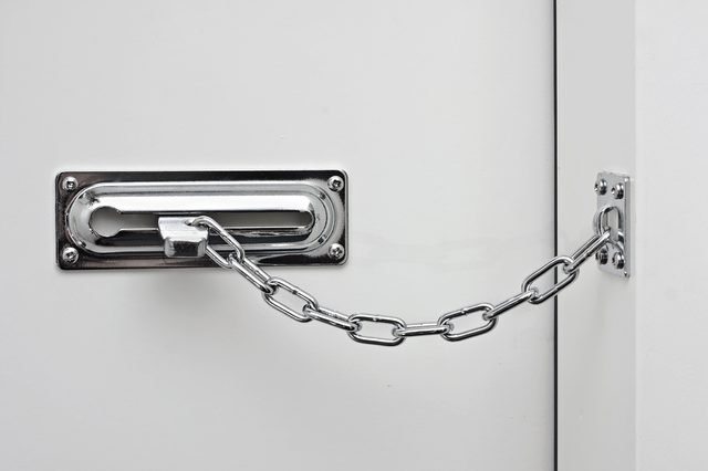 the white door is closed on a silvery chain