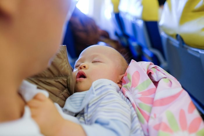 Adorable Baby Sleeping On Airplane ,Toddler boy sleeping on father's laps while traveling in airplane,Flying with children. Dad and sleeping 10 months old baby, Dad holding son:Shallow depth of field
