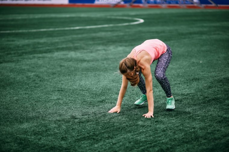 A beautiful muscular girl in leggings and a vest makes a bur pee at the stadium. Cross fit, fitness, healthy lifestyle