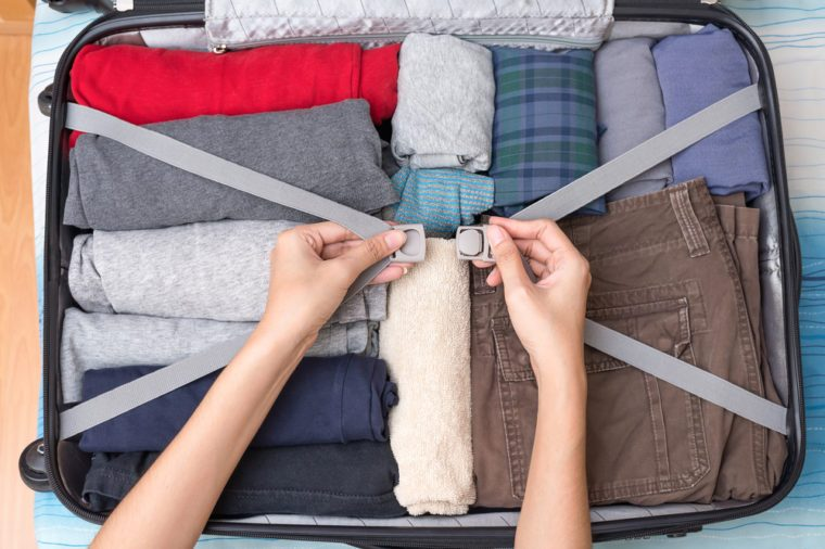 Close up, Woman's hands are pack suitcase, clothes in bag for travel. Top view.