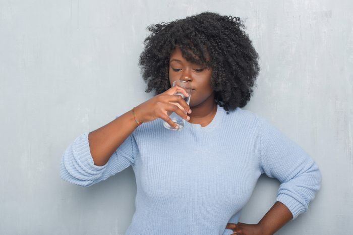 Young african american woman over grey grunge wall drinking a glass of water with a confident expression on smart face thinking serious