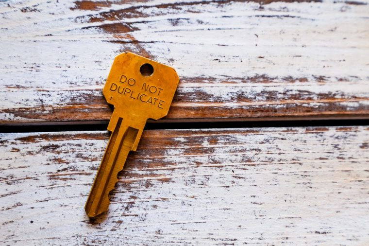 A single key on rustic wooden keyboard with do not duplicate written on it.