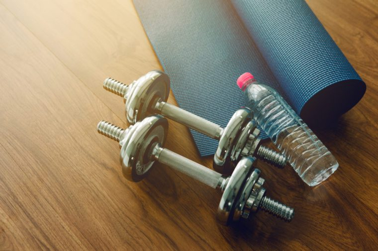 Pair of dumbbells with blue yoga mat on wood floor,flare light
