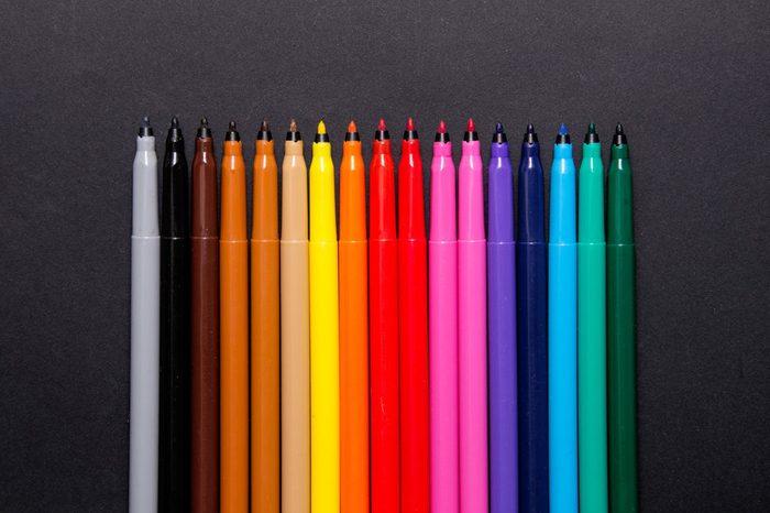Set of multicolor felt-tip pens, markers on black background; colorful felt pens