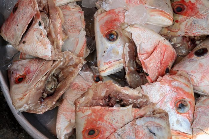 A bucket of colorful pink fish heads for sale at an Asian Market