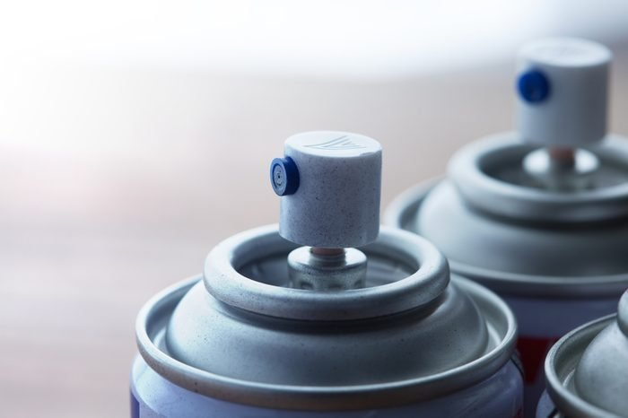 Aerosol spray cans nozzle close up. Several spray cans with light in background. Shallow depth of field.