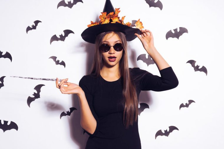 young beautiful sexy gothic girl in sunglasses changed into a witch for halloween, holds in her hands a magic wand