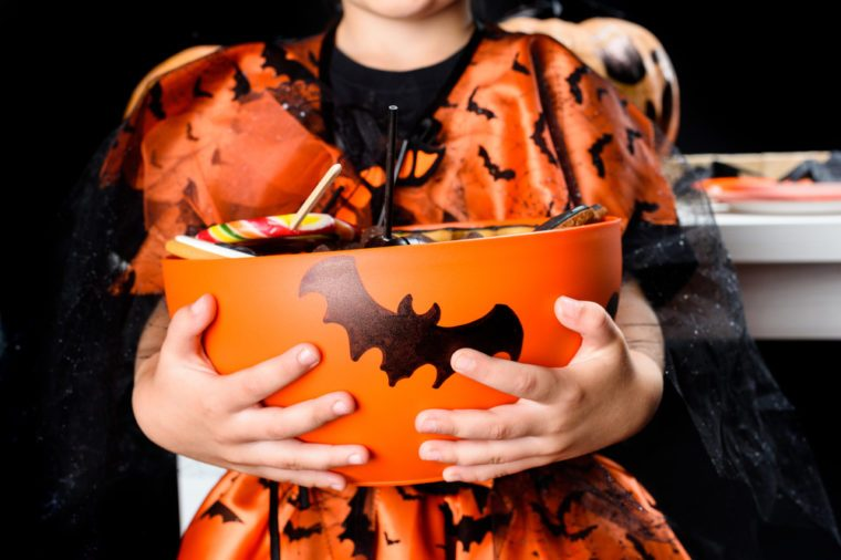 cropped view of child in witch costume of witch holding bowl full of halloween sweets, isolated on black