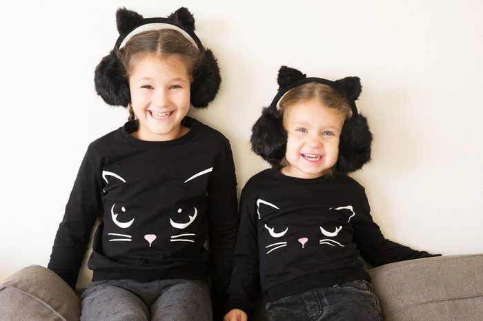 Two smiling little sisters dressed in costumes of black cats. Two children laugh fun. Children's holiday.