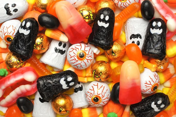 Halloween background of mixed candies, orange and black theme