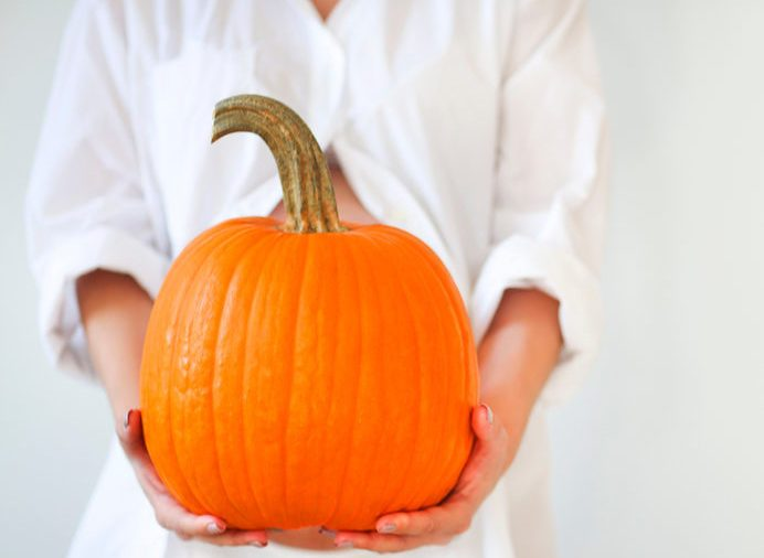 Pregnant woman with large pumpkin. Healthy concept. Close up