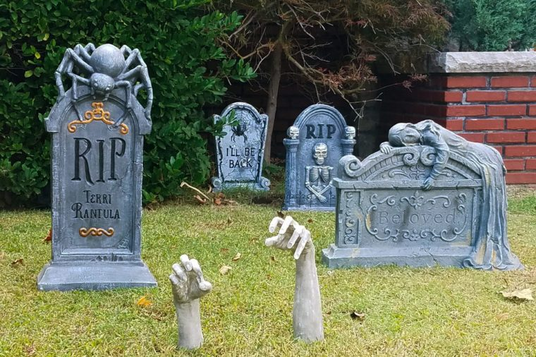 Halloween decorations of tombstones and hands reaching out of the ground in front of house