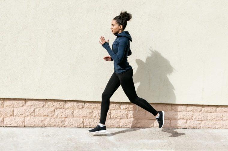Side view of young woman in sportswear jogging near wall