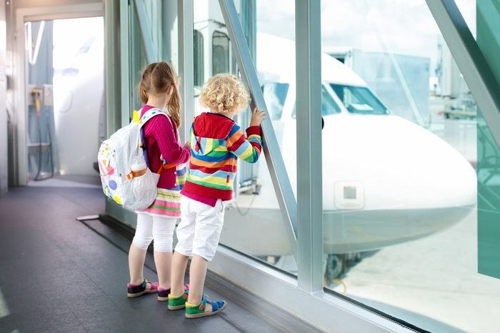 Kids at airport. Children look at airplane. Traveling and flying with child. Family at departure gate. Vacation and travel with young kid. Boy and girl before flight in terminal. Kids fly a plane