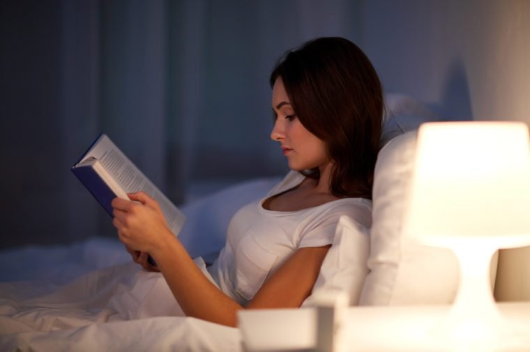 leisure and people concept - young woman reading book in bed at night home