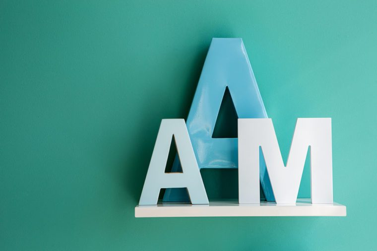 Letters A small and big size turquoise color and letter M on a white shelf. Shelf installed on a wall in a horizontal position. Fragment of interior decor.