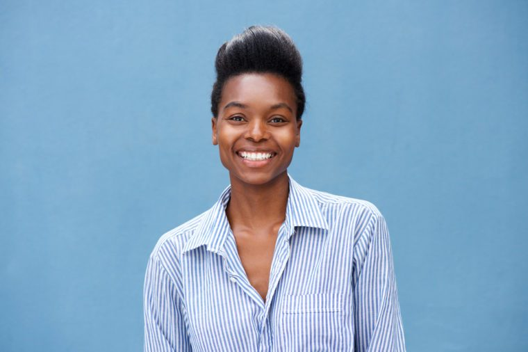 Close up portrait of beautiful young black woman smiling against blue background