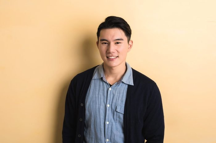 handsome Asian young man smile in the studio yellow background