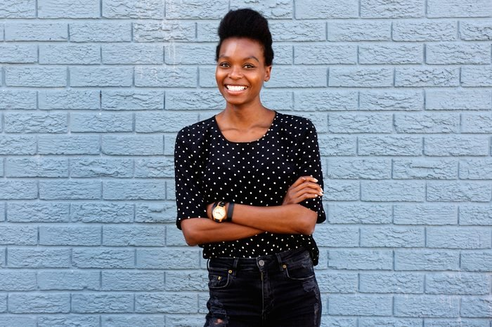 Portrait of attractive young african woman standing with her arms crossed against gray brick wall
