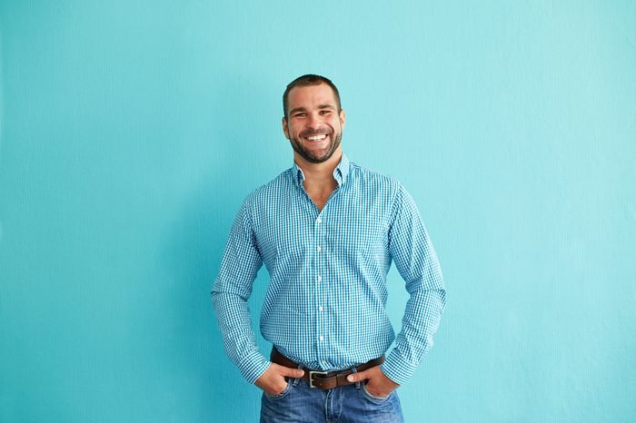 Smiling man standing in front of turquoise wall