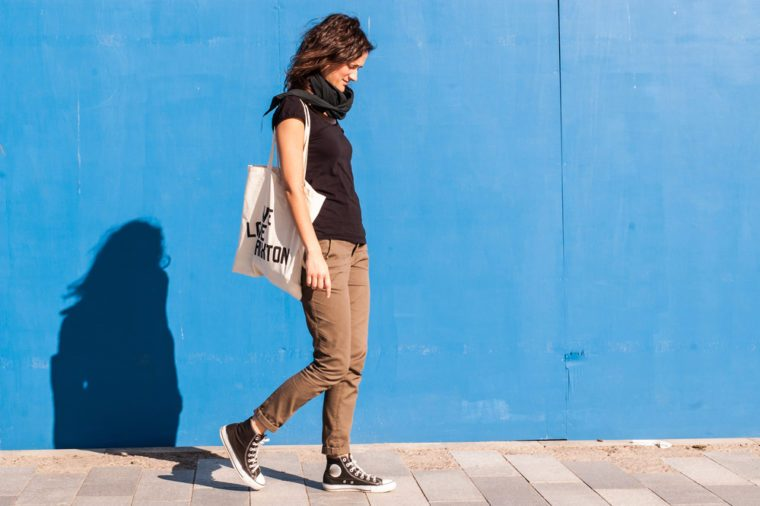 Young girl dressed in casual brown chinos, black sneakers and T-shirt walking on a street with blue wall in background.