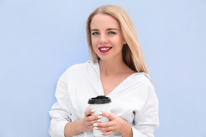 Beautiful young woman with cup of coffee near color wall