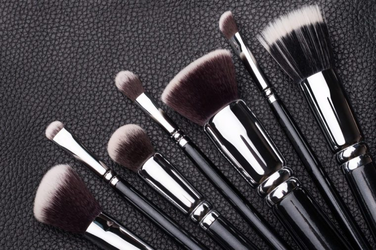 Set of professional makeup brushes over black leather background