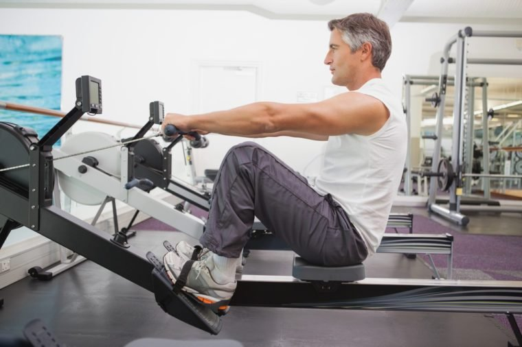 Fit man working out on rowing machine at the gym