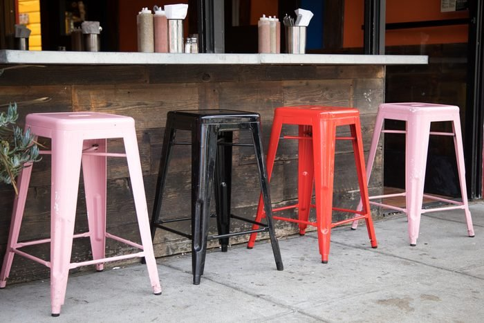 Left side of a row of red and pink square bar stools below a counter with condiment bottles and silverware container, in the outdoor sitting area of a taco restaurant