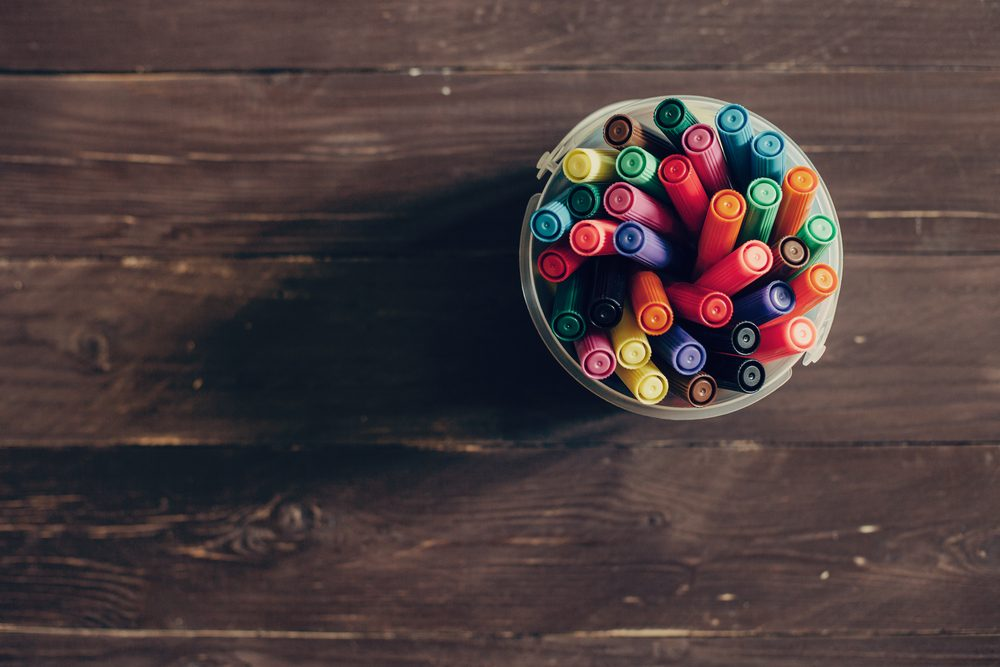 Top view, colorful felt pens on dark wooden table. Toned photo, shallow depth of field.