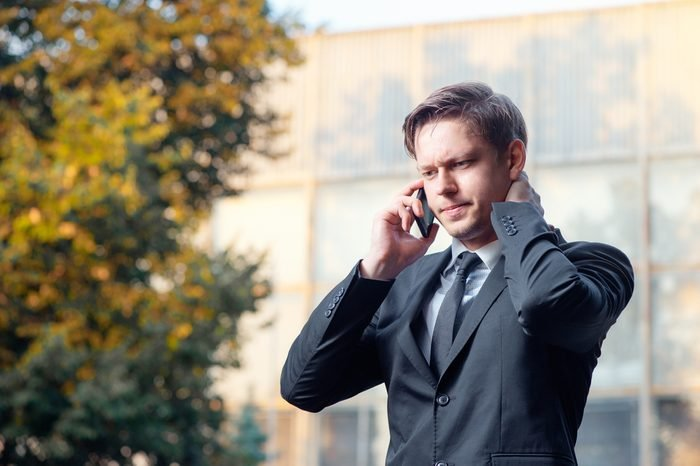 Bad news. Worried young businessman in suit and tie talking on the mobile phone while standing outdoors with office building in the background