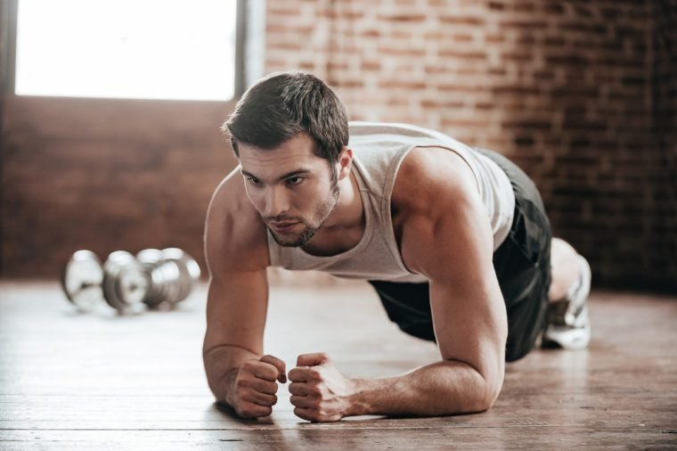 Plank it! Confident muscled young man wearing sport wear and doing plank position while exercising on the floor in loft interior