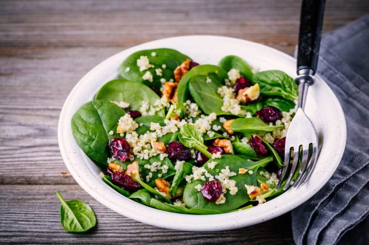 Green salad bowl with spinach, quinoa, walnuts and dried cranberries on wooden background