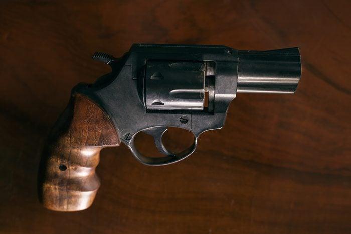 Revolver handgun over wooden background.