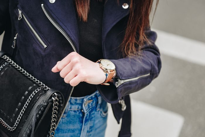 fashion blogger holding a trendy black purse and checking the time on her elegant watch. young stylish woman wearing a suede leather jacket, ripped jeans and black ankle boots.