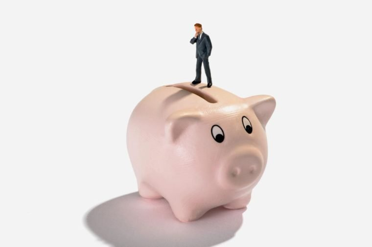 Studio shot close-up of a miniature figure man thinking of savings and profit while standing on a piggy bank against white background for copy space