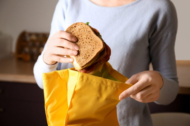 Mother packing food into school lunch bag indoors