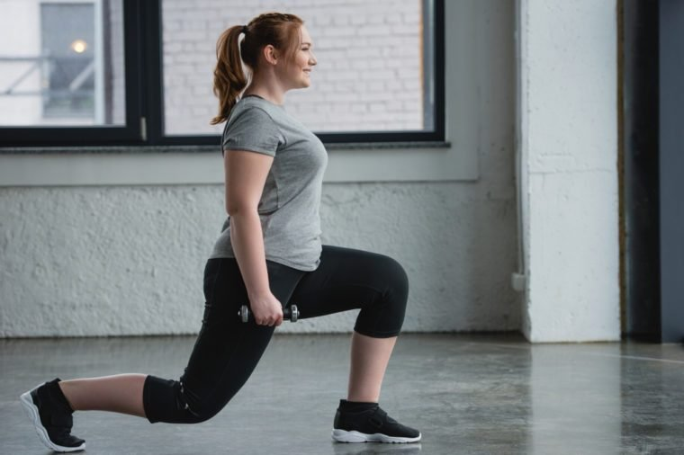 Obese girl performing lunges with dumbbell in gym