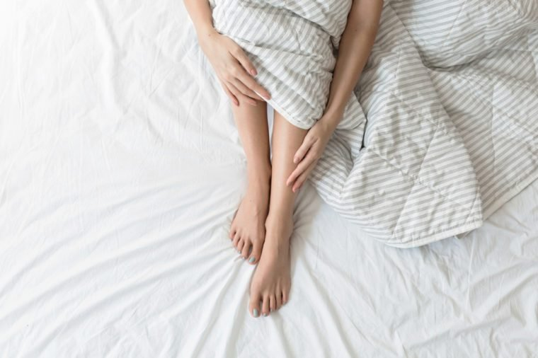 Legs and arms of unrecognisable woman sitting on her bed.