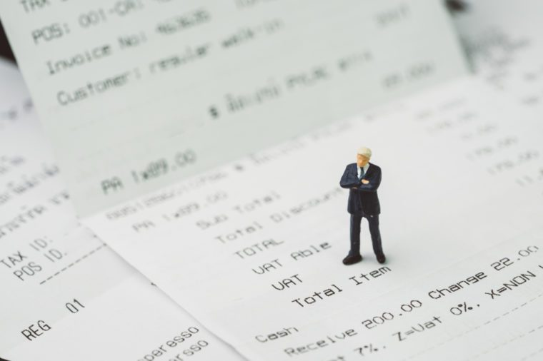 Tax, accounting and business expenses concept, miniature businessman figure standing on printed payment invoice or receipt around VAT line.
