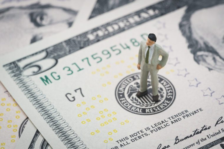 Miniature businessman leader standing and thinking on US Federal Reserve emblem on five dollars banknote as FED consider interest rate hike, economics and inflation control.