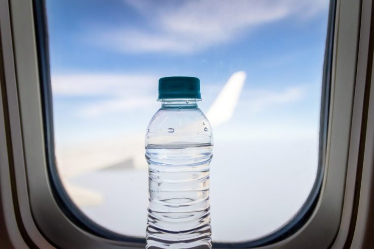 Bottle of water on clear sky from a plane. Travel concept.