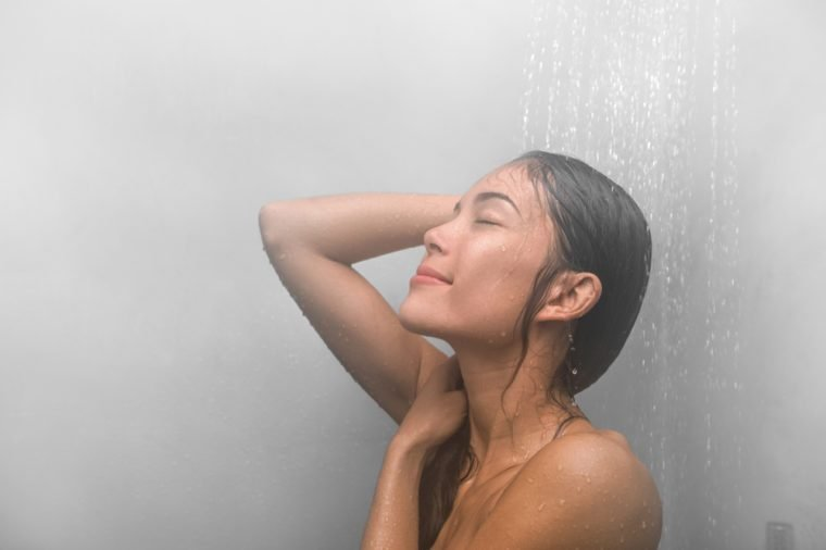 Woman taking a shower washing hair at home under warm water falling from luxury ceiling rain showerhead in clean white bathroom. Asian girl relaxing.