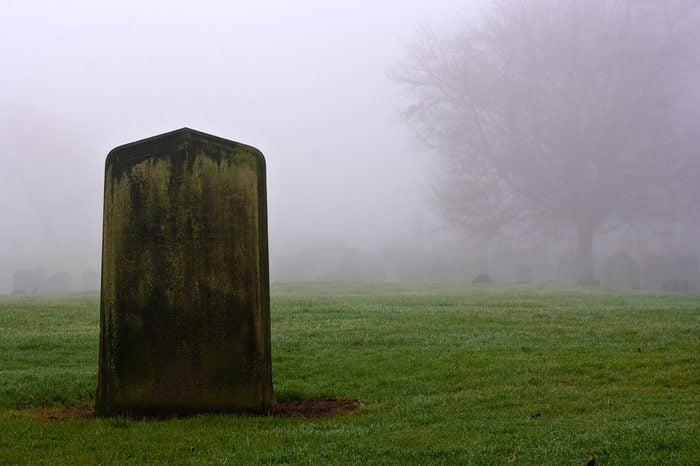 Single gravestone in a spooky graveyard on a foggy day