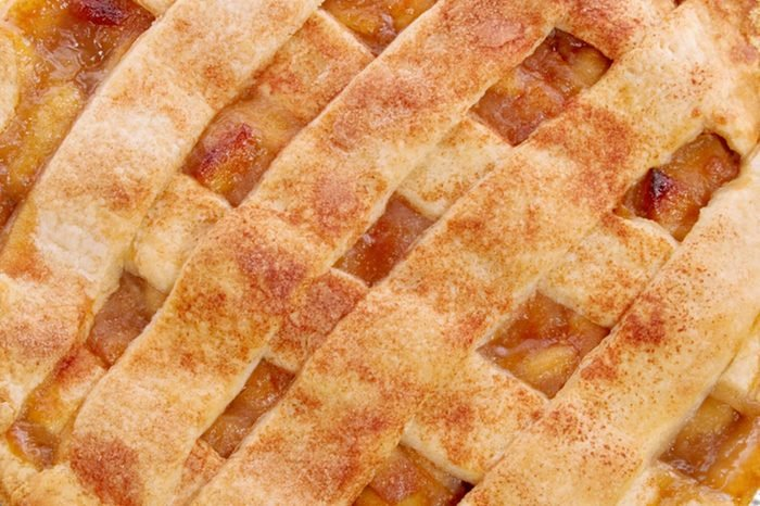 homemade whole apple pie with a lattice pastry crust covered with cinnamon and granulated sugar. The background is a black place mat.