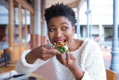 Close up portrait of a happy young woman eating pizza at restaurant