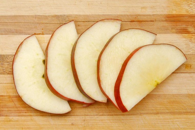 Sliced apple isolated on wooden board