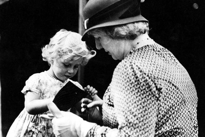 Various Princess Margaret selling white heather at garden fete