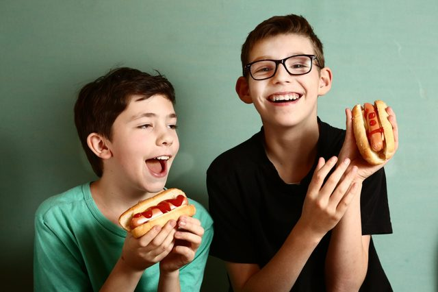 young boys eating hot dogs