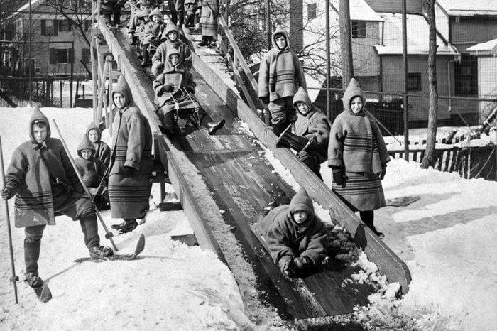 Children sliding on a wooden chute at an open-air school